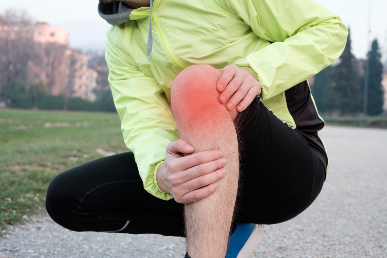 Runner with injured knee while training in the city park in cold weather