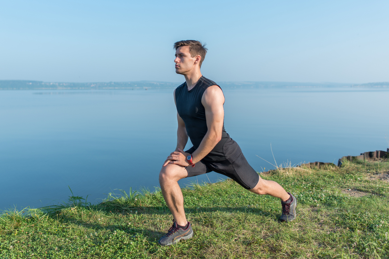 Young fit man stretching legs outdoors doing forward lunge